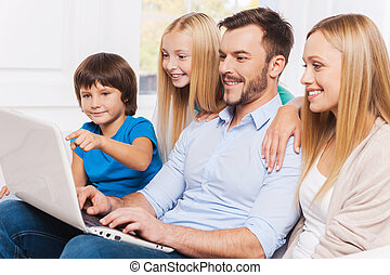 Surfing the net together. Side view of happy family of four...