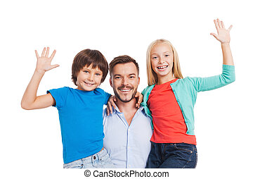 Our father is the best! Happy father carrying two cheerful children and smiling while standing against white background