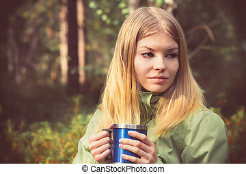 Young Woman with metal touristic tea cup Outdoor Lifestyle and Hiking concept with forest on background