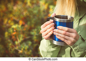 Metal touristic tea cup in Woman hands Outdoor Lifestyle and Hiking concept with forest on background