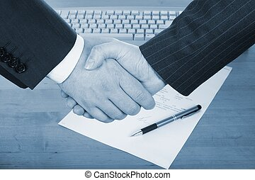 businessmens handshake over contract and pen in blue tone