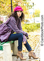 Young beautiful woman sitting on a bench in a city park -...