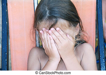 shy girl - a caucasian young girl covering her face with her...