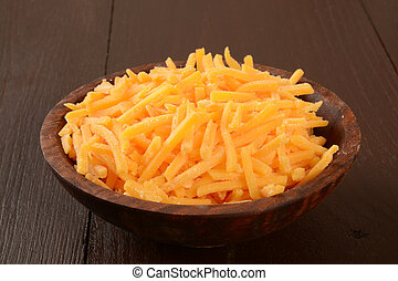 Bowl of grated cheddar cheese