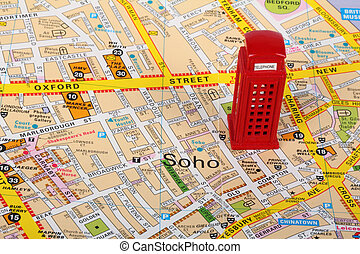 Small model of a red phone box  on top of a map of London