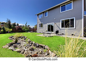 Beautiful backyrd landscape design with lawn and rocks
