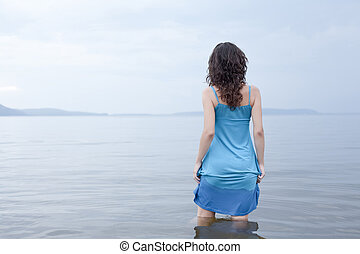 Lonely woman stands in water. Blue tones