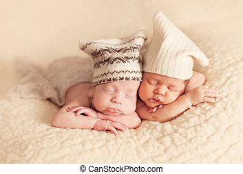 Newborn twins sleeping on the beige blanket together
