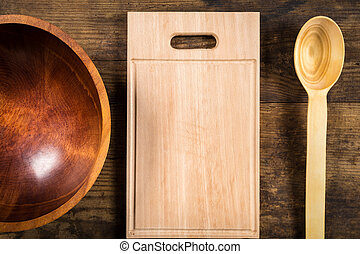 Blank cutting board with ladle and bowl on dark wooden...
