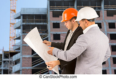 Two architects discussing a building blueprint