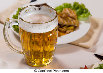 Close up Mug of Beer Beside Main Dish on White Table