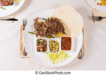 Grilled Steak Fajitas with Fixings on Plate - Overhead of...