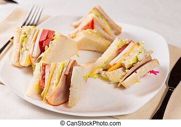 Close Up of Triple Decker Sandwich on Plate at Place Setting