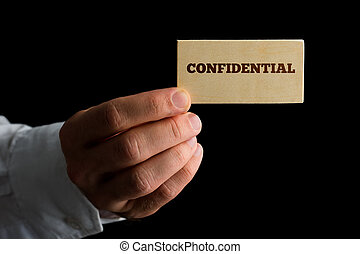 Man with a business card reading - Confidential - Close up...