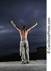 Man with his arms wide open outdoor against dark sky