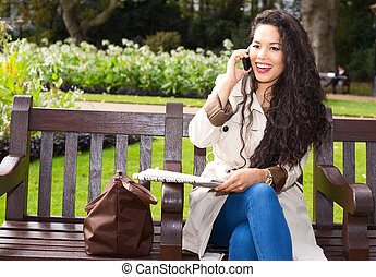 young woman talking on the phone with newspaper