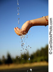 fresh water falling on children hands - clear water falling...