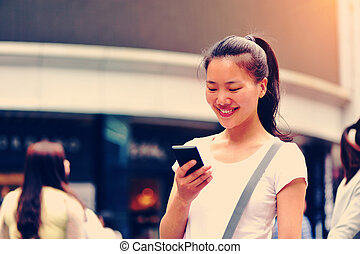 woman using cellphone on street - beautiful young asian...