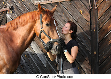 Portrait of happy woman and brown horse near the barn