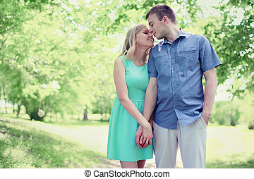 Lovely tender young couple in love walking in sunny spring...