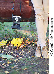 Stylish woman with retro vintage camera in autumn day