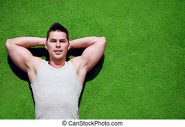 Fitness, sport - concept Handsome man relaxing on the grass...