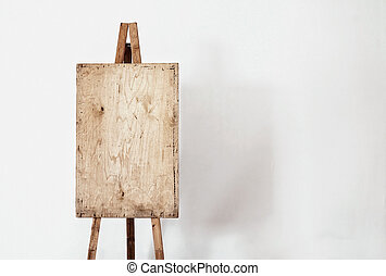 Blank grunge easel in a light room, art background