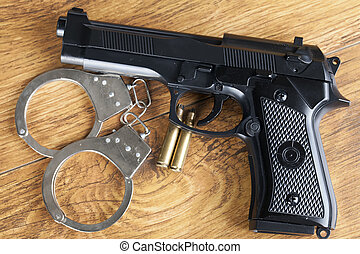 Crime concept with handgun, handcuffs and bullets on wooden...