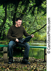 young businessman working on laptop outdoor - one young...