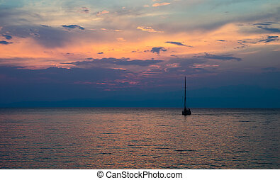 A beautifull sunset view of a fishing boat on calm ocean...