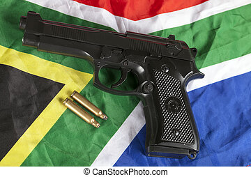 Handgun and brass bullets on South African flag