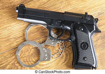 Handgun and handcuffs on wooden background