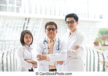 Asian medical team standing inside hospital building - Asian...