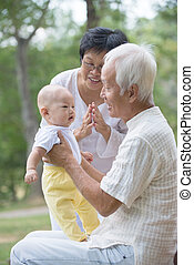 asian grandparents playing with baby grandson at outdoor