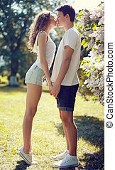 Pretty young couple in love, sensual kiss in sunny warm day