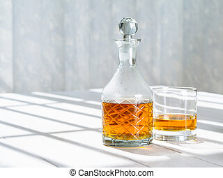 Whisky decanter and rocks glass by the window - Photo of a...