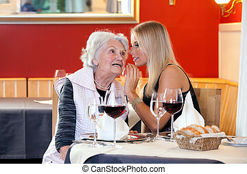 Old and Young Women Talking at Restaurant Table with Glasses...