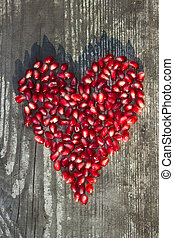 pomegranate seeds in heart shape on grey wooden background