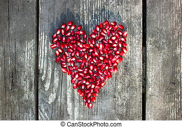 pomegranate macro seeds in heart shape on grey wooden...