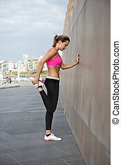 Athletic woman stretching her thigh