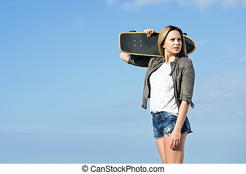 Skateboarding girl looking back - Pretty girl carrying a...