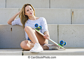 Skater girl - Young woman, sitting comfortably on concrete...