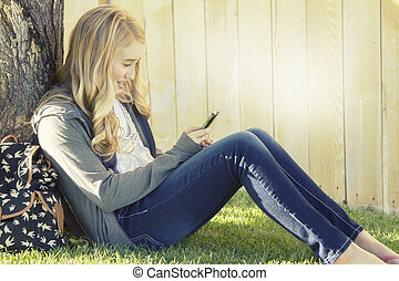 Teenage girl smiling while using a cell phone, texting,...