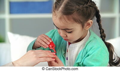 Nail Art Master - Focus on toddler applying nail polish on...
