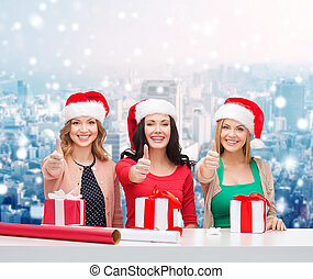 smiling women in santa helper hats packing gifts -...