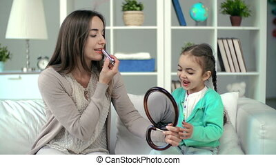 Do Like Mother Does - Mother showing daughter lipstick...