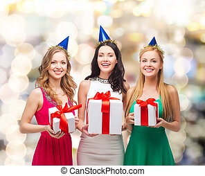 smiling women in party caps with gift boxes - presents,...