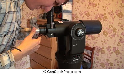 Astronomer sets the camera to the telescope