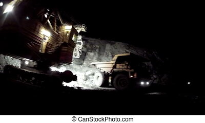 The excavator loads dump truck. Night mode.