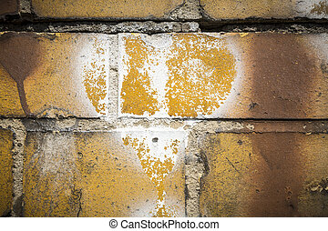 faded white heart symbol on a grungy yellow brick wall